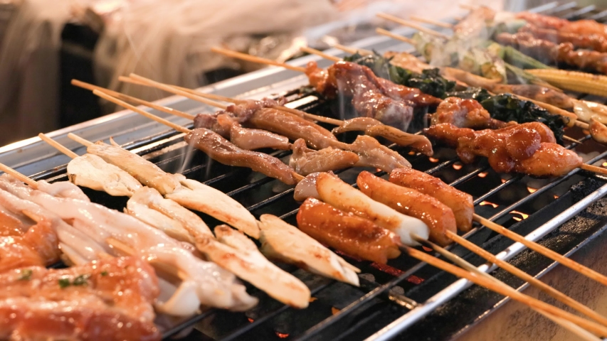 A street vendor is grilling assorted BBQ meat and vegetable on bamboo skewers with sauce. Street food snack selling at traditional market in Chiang Mai, Thailand. | Shutterstock HD Video #1054733918