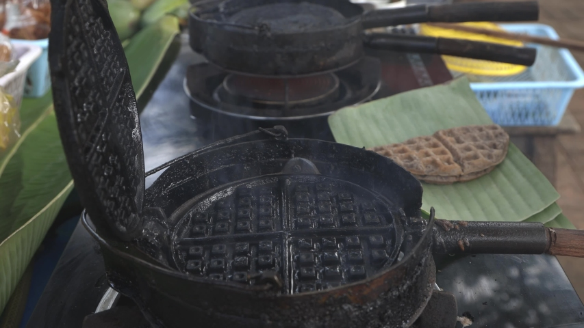 Street food vendor is preparing Thai style waffle a kind of ancient Thai dessert/snack, made of rice flour, coconut milk, etc. with assorted filling like shredded young coconut meat. | Shutterstock HD Video #1054733930