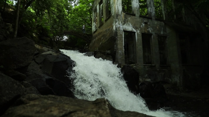 Waterfall pouring down the side of an abandoned mill in Gatineau Park, Quebec. | Shutterstock HD Video #1054733936