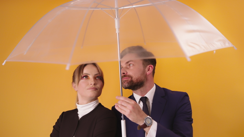 A Professional Man Holding A Transparent Summer Umbrella Standing Beside A Lovely Woman Against Yellow Background - Half-Body Shot | Shutterstock HD Video #1054733945