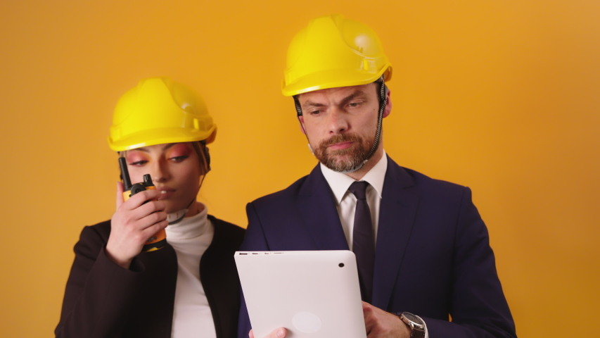 Portrait Of Two Architects Wearing Construction Hard Hats - A Woman Holding A Radio Near Her Mouth While A Man Holding A Tablet Looking Annoyed Against Yellow Background - Half-Body Shot | Shutterstock HD Video #1054733948