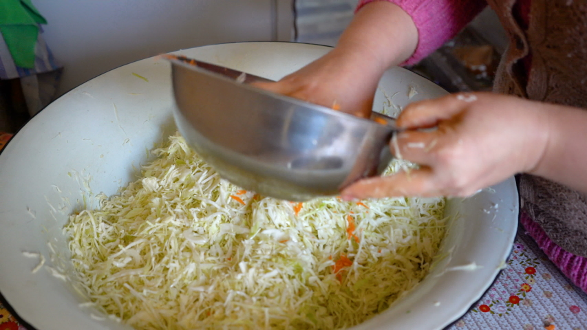 Ferment cabbage with carrots,harvesting cabbage with carrots for the winter, a woman adds carrots to cabbage and stir by hand | Shutterstock HD Video #1054734323