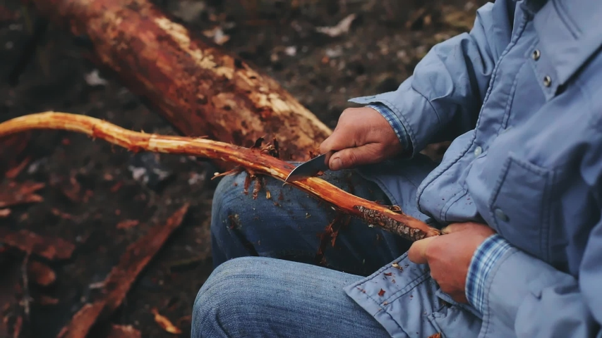 A man cuts a small knife freshly cut a small stick in the forest. Camping, tourism or mushroomer.  Hunter man with a knife cut a wooden stick. A man lumberjack is sharpening a wood stick for a bonfire | Shutterstock HD Video #1054734380