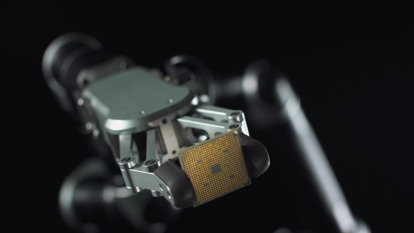 Modern technology and artificial intelligence, futuristic robot arm holds a microprocessor, shows the microchip to the camera, black background. | Shutterstock HD Video #1054734407