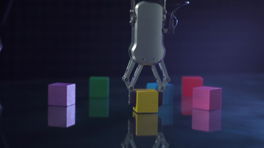 Futuristic robot hand picks up and moves colored cubes, artificial intelligence controls the robot's motor skills. | Shutterstock HD Video #1054734479