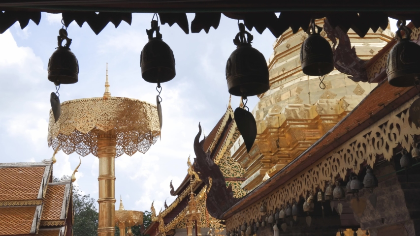 Row of small temple bells hanging from the eaves with background of gold plated chedi and buildings at Wat Phra That Doi Suthep, one of the most famous Buddhist temple in Chiang Mai, Thailand. | Shutterstock HD Video #1054735481