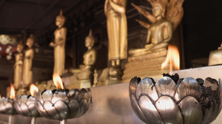 Close-up shot of candles withing flame in lotus-shapes candle holders with row of golden Buddha statues on the background in a Buddhist temple.