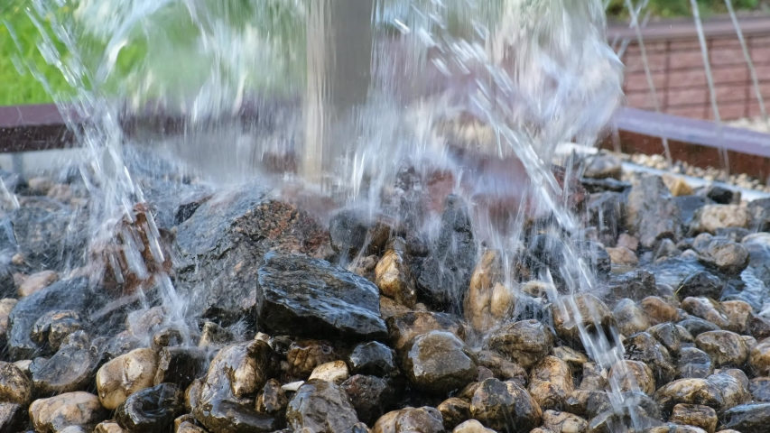 Spray on the stones of a decorative fountain and waterfall close-up. | Shutterstock HD Video #1054735562