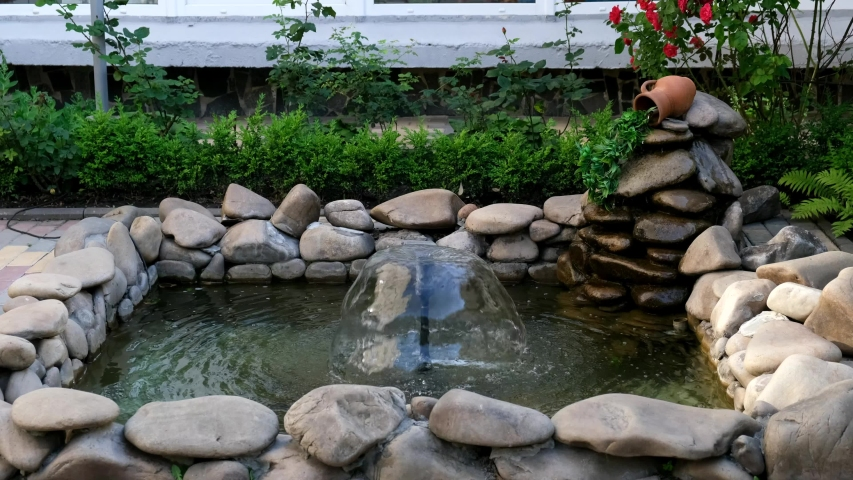 A small decorative mushroom fountain in a stone pool with a waterfall from a pitcher. Landscape design. | Shutterstock HD Video #1054736273
