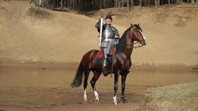Video footage, a young adult man in knightly armor rides a horse on water in a river along a sandy shore