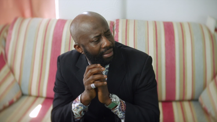 A sad depressed African male sits holding his head in his hands. He shakes his head in despair. The bearded businessman is wearing a black suit jacket and is siting on a sofa at home. | Shutterstock HD Video #1054736504