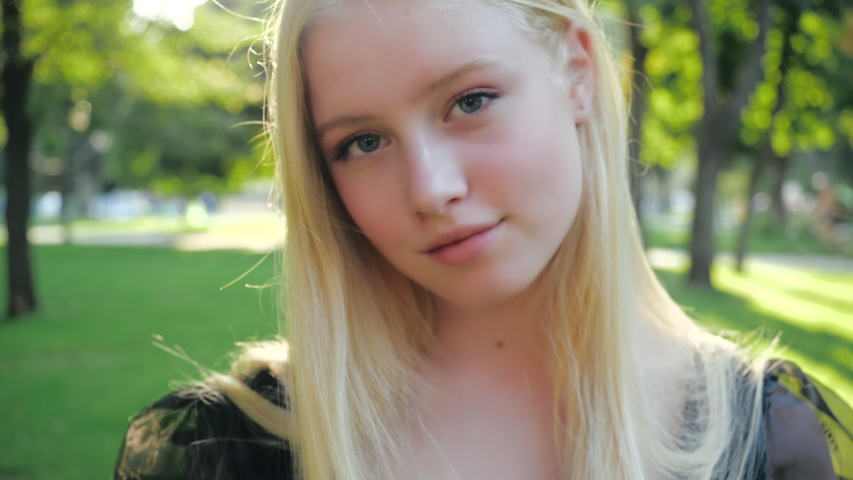 Attractive European blonde teen girl with natural make-up walks in nature on a sunny day. Beautiful fashionable teenage model soft smiles, posing outdoors straightened long hair. People style concept Royalty-Free Stock Footage #1054736660