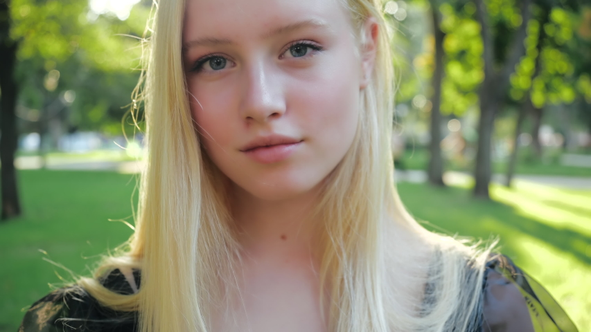 Attractive European blonde teen girl with natural make-up walks in nature on a sunny day. Beautiful fashionable model soft smiles, posing outdoors and straightens her long hair. People style concept. | Shutterstock HD Video #1054736660