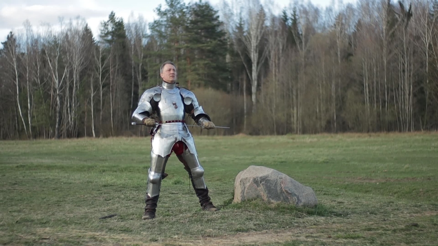 Video footage, a knight on foot in armor and holding a sword in his hands shows combat attacks on the battlefield. | Shutterstock HD Video #1054736690