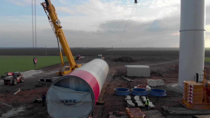 Building process of wind energy power tower, windmill under construction. Transportation of tower part, assembling the pillar. Green, clean, renewable energy. Aerial footage. Royalty-Free Stock Footage #1054736738