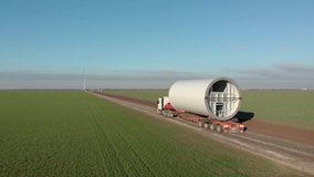 Building process of wind energy power tower, windmill under construction. Transportation of tower part, assembling the pillar. Green, clean, renewable energy. Aerial footage.