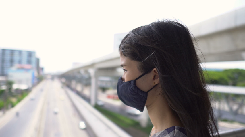 Portrait of Worried Young Asian Woman Wearing Face Mask in Urban Environment - New Normal After Covid-19 | Shutterstock HD Video #1054737008