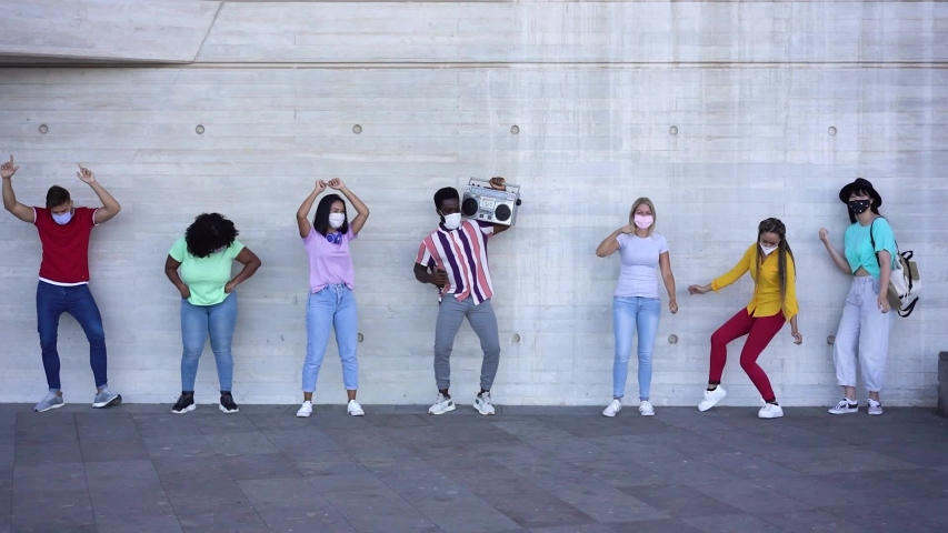 Happy people from different races and culture dancing outdoor while listening music from old boombox stereo. Young friends having fun together - Alternative party during coronavirus outbreak | Shutterstock HD Video #1054737419