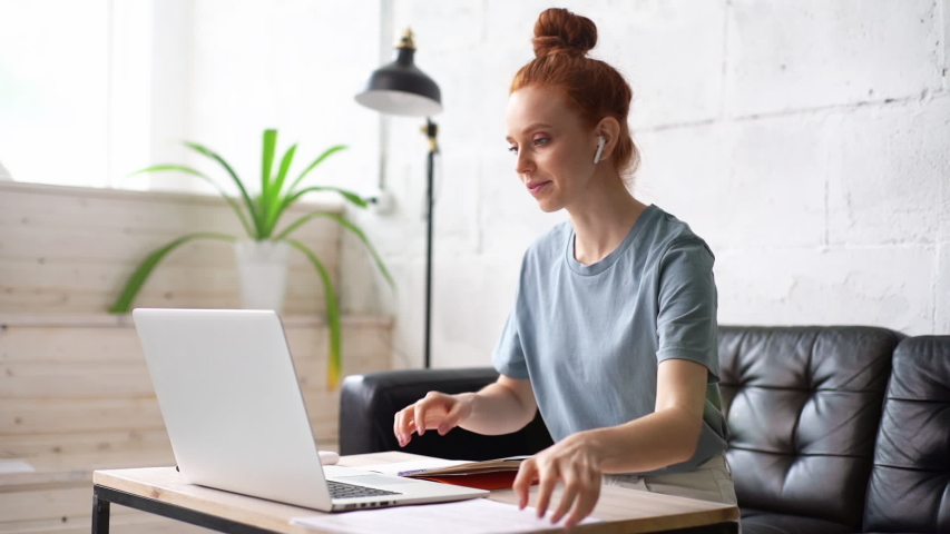 Happy redhead young woman is speaking on video call with friend client colleague using laptop computer at home office. Portrait of emotional business lady gesturing saying hello on video call online. Royalty-Free Stock Footage #1054737518