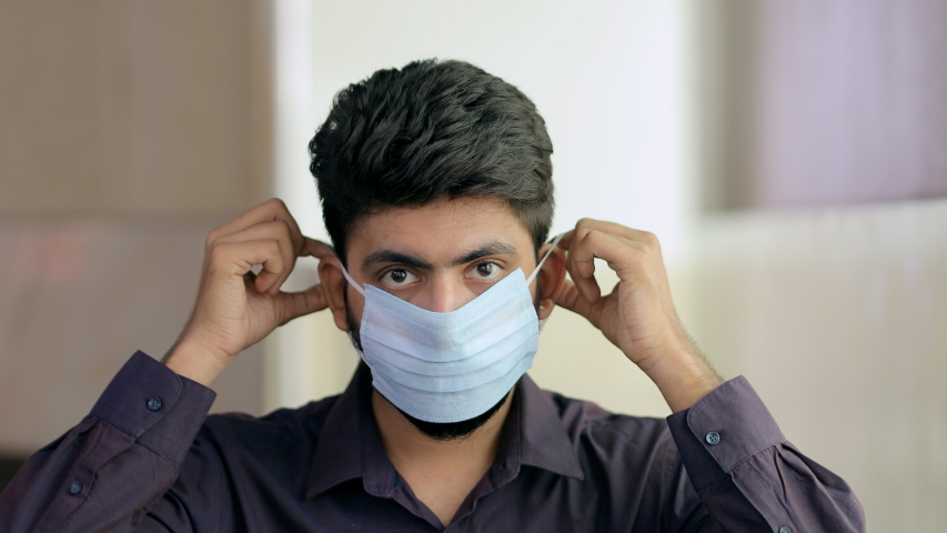 Closeup shot of a young man using a medical mask during the Covid-19 pandemic. Handsome Indian guy wears a surgical mask and shows a thumbs-up sign to protect himself from coronavirus Royalty-Free Stock Footage #1054737911