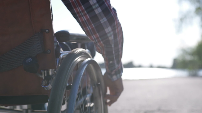 A man in a wheelchair walks on the waterfront Royalty-Free Stock Footage #1054740098