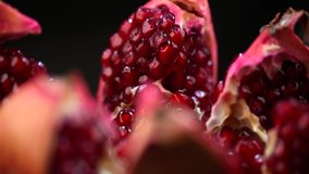 Pomegranate fruit. Fresh and ripe Pomegranates rotating over black Background. Organic Bio fruits close-up. Diet, dieting concept. Vegan food. Slow motion 4K UHD video.