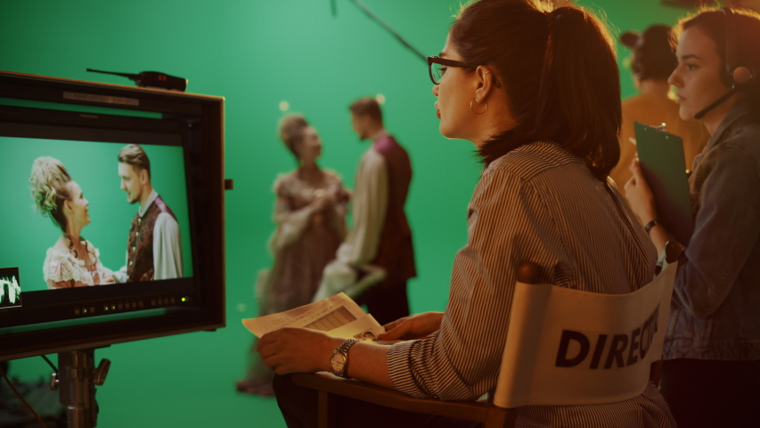 Famous Talented Female Director in Chair Looks at Display talks with Assistant while Shooting Blockbuster. Green Screen Scene in Historical Drama. On Film Studio Set Crew Doing High Budget Movie Royalty-Free Stock Footage #1054740608