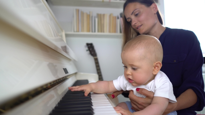 A cute baby boy playing a white piano with his mommy teaching him and holding him in her lap 4K