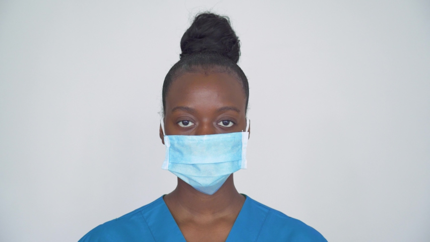 Brave proud female african american scrub nurse wear face mask blue uniform look at camera, tired black woman doctor head shot portrait. Medical staff corona virus covid19 pandemic outbreak protection Royalty-Free Stock Footage #1054741859