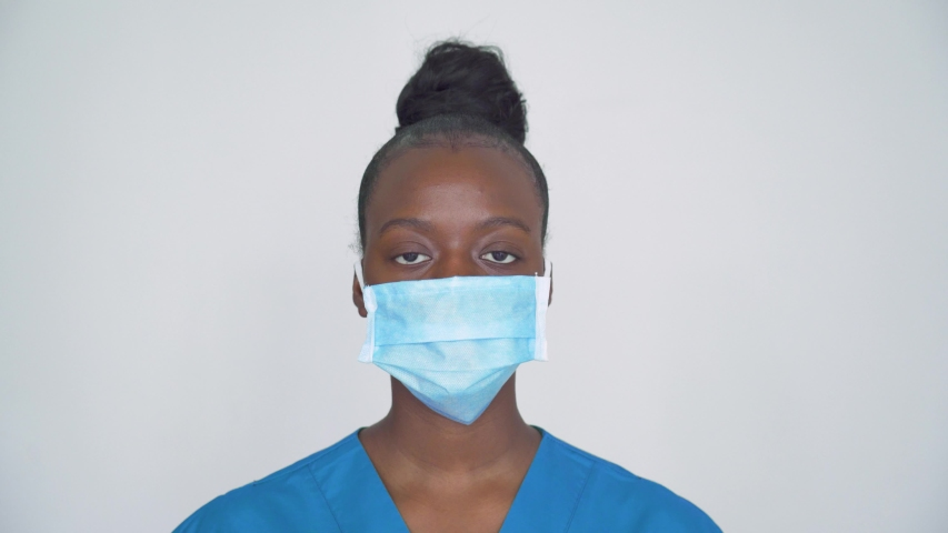 Brave proud female african american scrub nurse wear face mask blue uniform look at camera, tired black woman doctor head shot portrait. Medical staff corona virus covid19 pandemic outbreak protection