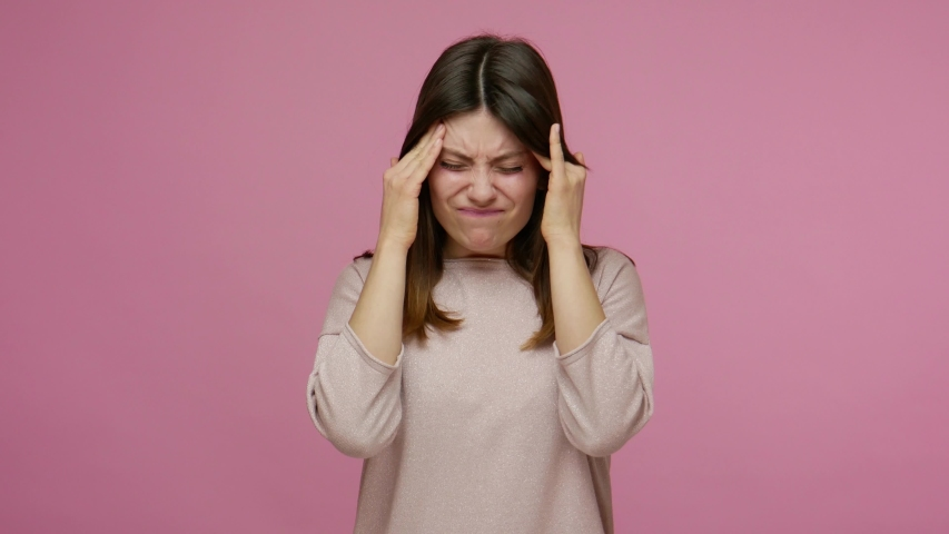 Depressed worried young brunette woman suffering intense migraine, rubbing head temples and frowning from headache, feeling stress tension of troubles. indoor studio shot isolated on pink background | Shutterstock HD Video #1054742270