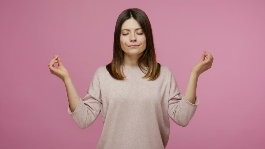 Meditation, peaceful mind. Calm brunette woman raising hands in mudra gesture and closing her eyes to relax, mental yoga practicing, concentration. indoor studio shot isolated on pink background | Shutterstock HD Video #1054742420