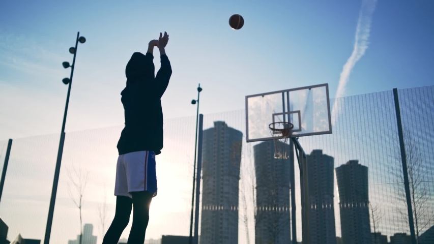 Back view of unrecognizable player throwing ball in a basketball hoop, the ball hits the ring and scores. Slowmotion shot