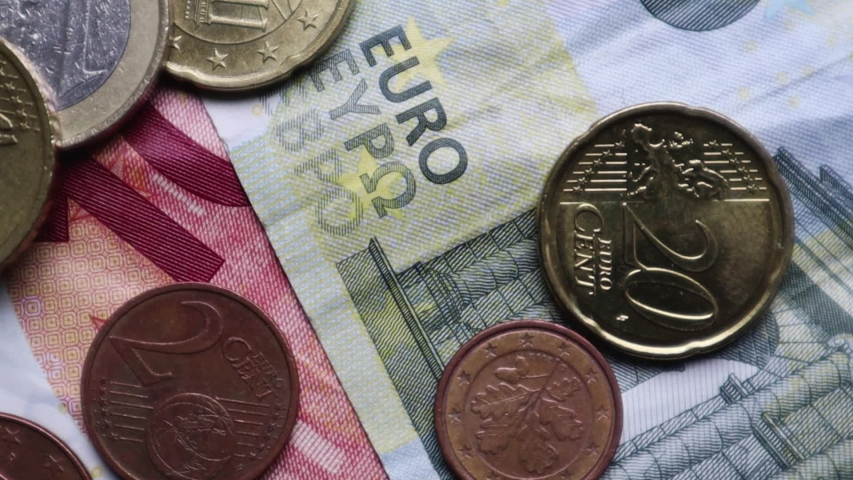 Euro banknotes and coins rotate as background. Shot looking down on a euro currency rotating. Coins are stacked on top of each other in different positions. Money concept. | Shutterstock HD Video #1054744184