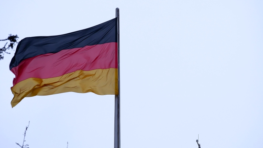 Flag of Germany on the roof of the Reichstag building (Deutscher Bundestag). Fabric flags flutter in the wind on a cloudy day. Concept of policies, laws and governance in the European Union.