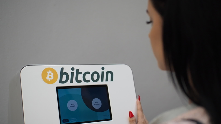 Woman making a bitcoin withdrawal from the cryptocurrency ATM machine in HD VIDEO. Blockchain technology in real people life concept. Close-up. Royalty-Free Stock Footage #1054745102