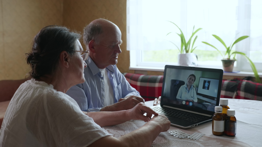 family elderly couple man and woman consult a doctor online about a disease and symptoms during a telemedicine video call, using modern technology while sitting in a computer room Royalty-Free Stock Footage #1054746341