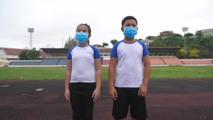 Asian Boy And Girl Takes Off Mask At Stadium