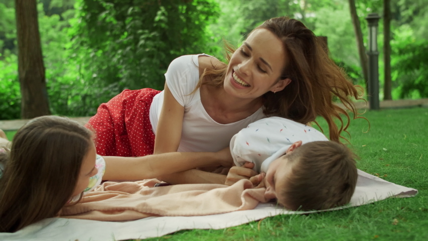 Laughing mother and children lying on blanket in summer park. Positive family relaxing together in forest. Smiling woman tickling boy. Happy family spending weekend together