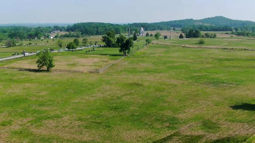 Aerial of grassy Civil War battlefield, Gettysburg, PA, monuments honoring fallen Union and Confederate Army soldiers