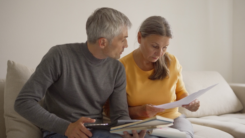Medium shot of senior couple sitting on sofa at home and calculating home finances. Retired couple arguing while discussing bills
