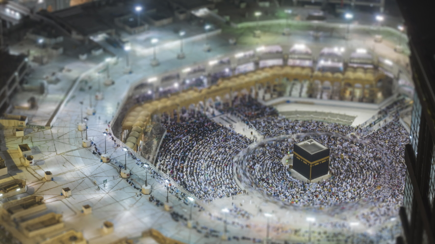 Tilt shift Time lapse sunrise of Muslim pilgrims circling around the holy Kaaba at dawn and praying inside al Masjid al Haram in Mecca, Saudi Arabia. Zoom out motion timelapse. Prores UHD