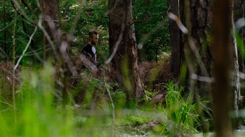 Man in black walking in green forest between trees to a lake on a sunny day and enjoys nature - cinematic slow motion   Shutterstock HD Video #1054751846