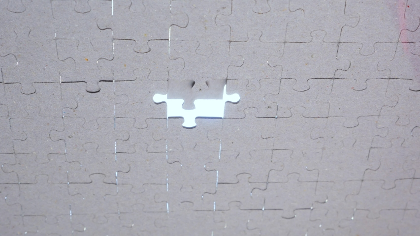 Last piece of puzzle for whole picture. Concept: cooperation, teamwork, creativity, access solution A creative completes the white jigsaw puzzle putting the last missing piece