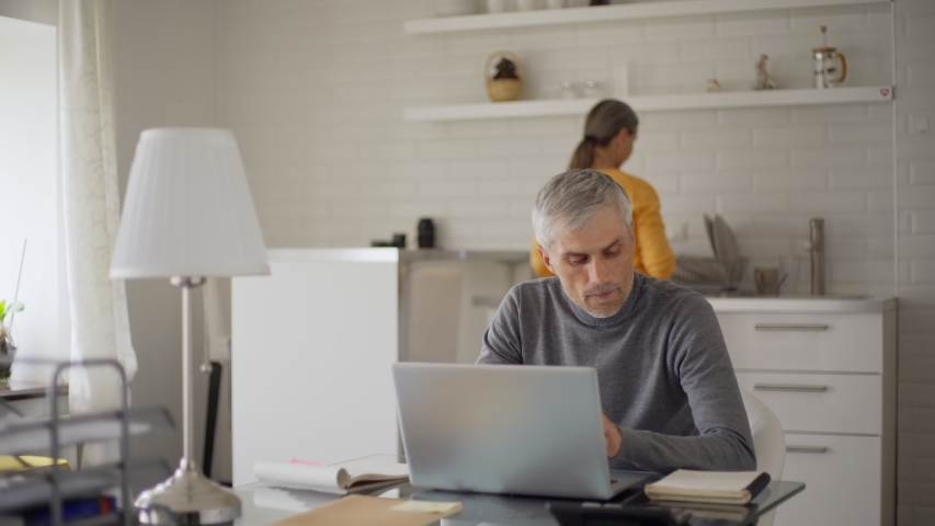 Senior man calculating home finances on laptop sitting at table at home. Caring wife bringing tea and cookies for him, embracing and looking at pc screen. Senior couple discussing budget and smiling