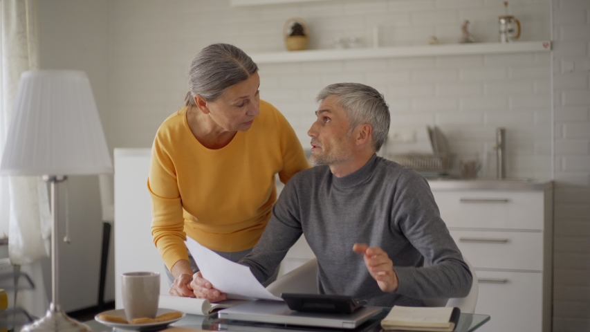 Senior man calculating home finances on laptop sitting at table at home. Caring wife bringing tea and cookies for him. Man closing laptop and using calculator. Senior couple discussing bills