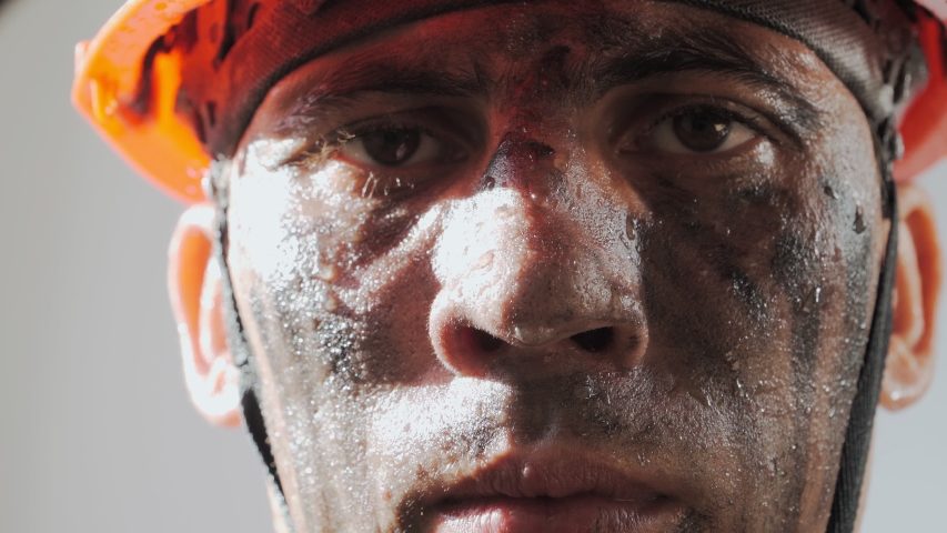 Portrait Dirty Mine Worker. Sweaty Exhausted Man in a Hard Hat. Filthy Job and Physical labor. Coal mining. People Working Equipment. Close up. Royalty-Free Stock Footage #1054760621