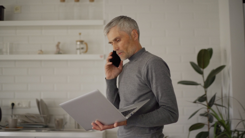 Senior man talking on cell phone pacing back and forth at home with laptop in his hands. Businessman finishing call, sitting down at desk, working on pc and thinking. Online and remote work concept