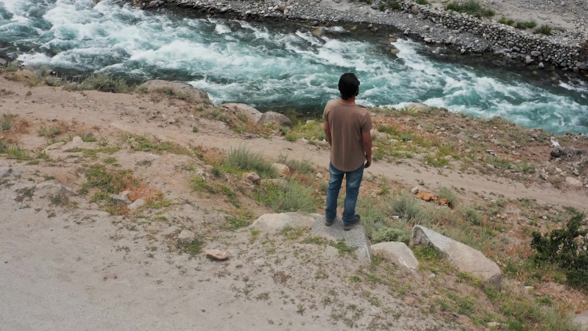 Pakistani Man looking into Wild River, North Pakistan, Aerial Forward