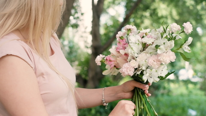 Beautiful woman florist collects a magnificent bouquet of flowers for the holiday. She puts flowers out of a vase florist tools. Business concept. Shop. 20-25 years. outdoor work